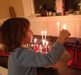 Young Boy Lighting a Menorah