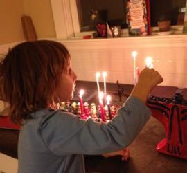Young Boy Lighting a Menorah